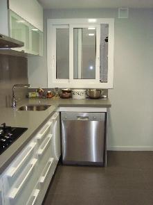 Cocina toda reformado con pavimento porcelánico, enyesado de paredes y pintado con mobiliario blanco brillo y silestone.